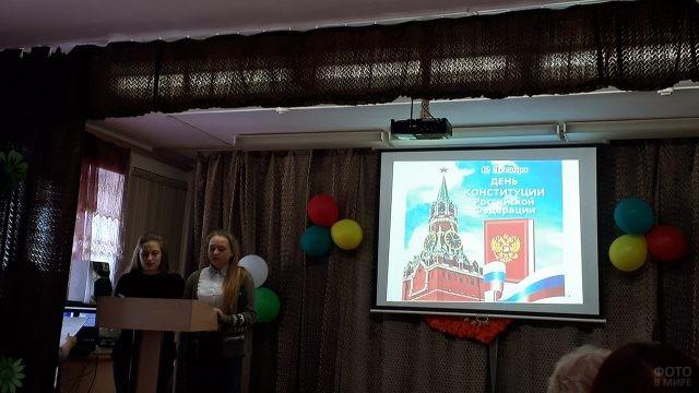 Две студентки делают доклад на сцене