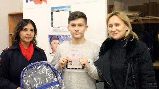Мама, подросток с паспортом и представительница МВД с подарком