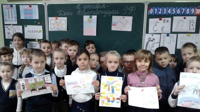Первоклассники у доски с рисунками в честь Дня Конституции
