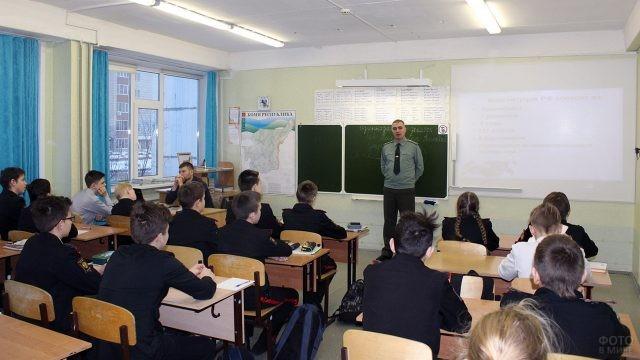 Росгвардеец у доски рассказывает школьникам о Конституции