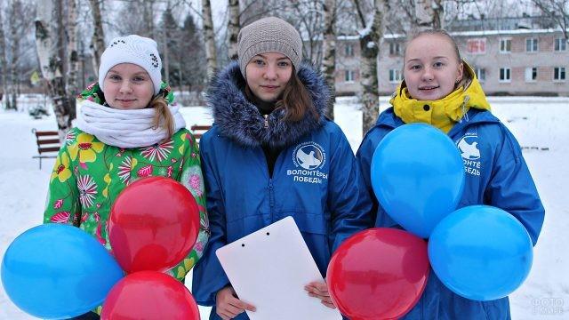 Школьницы-волонтёры с шариками на заснеженной улице