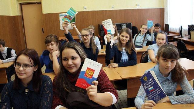 Школьницы за партами с Конституцией в руках