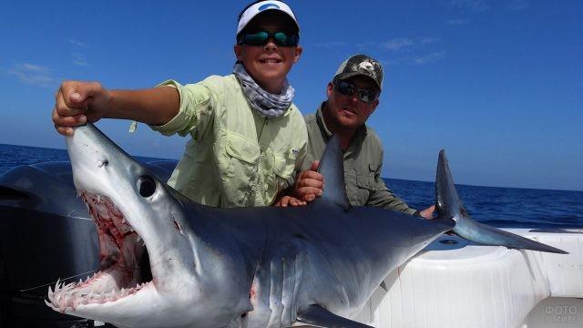 Мальчик с отцом держат пойманную акулу