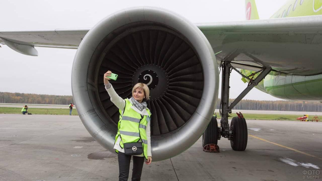 Девушка фотографируется у турбины во время экскурсии по Домодедово