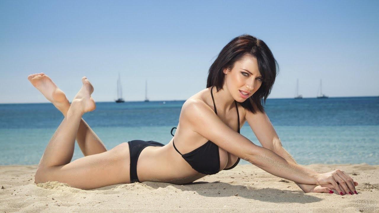 Брюнетка в купальнике на песчаном пляже