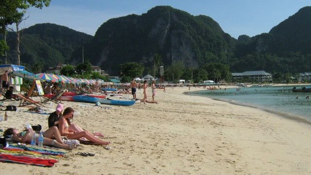Девушки загорают на песчаном пляже