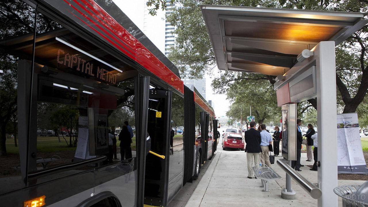Автобус с распахнутыми дверьми на остановке в мегаполисе