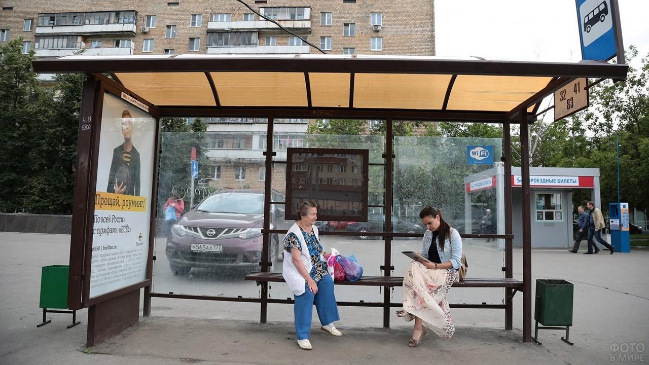Девушка и пенсионерка сидят на остановке