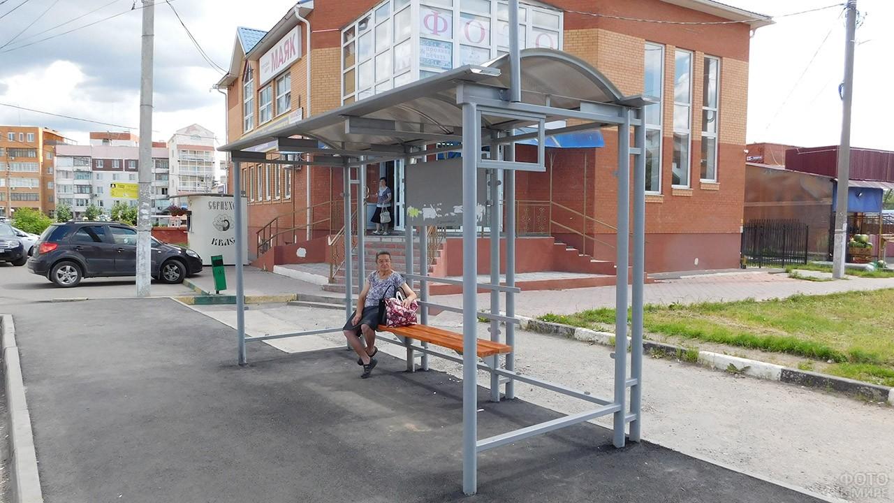 Пенсионерка сидит на автобусной остановке