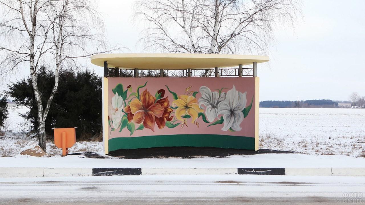 Расписанная цветами остановка в заснеженном поле