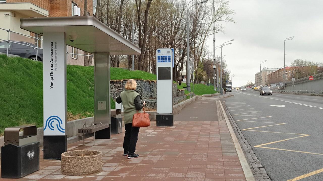 Женщина ждёт автобус на современной остановке