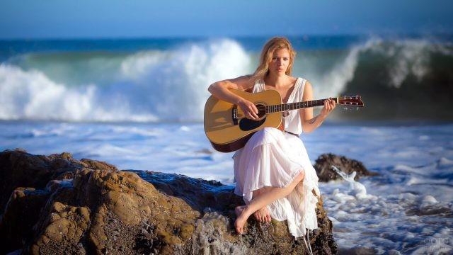 Девушка играет на гитаре у моря
