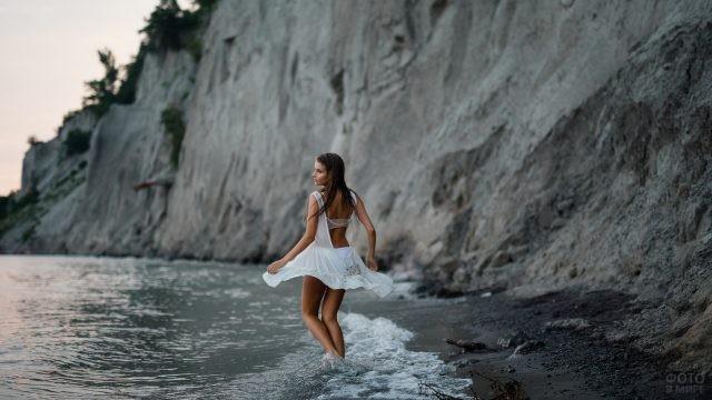 Девушка кружится в море у скал