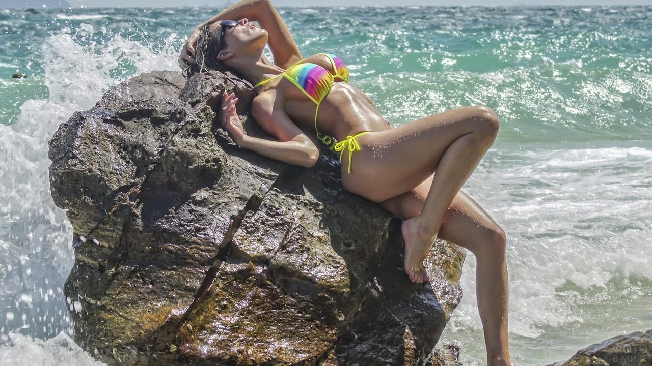 Девушка с капельками воды на теле лежит на камне