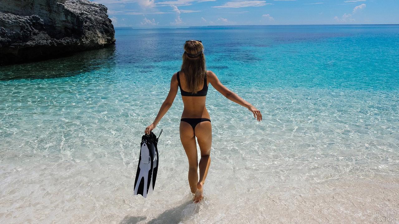 Девушка с ластами идёт по воде