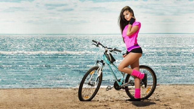 Девушка с велосипедом на море