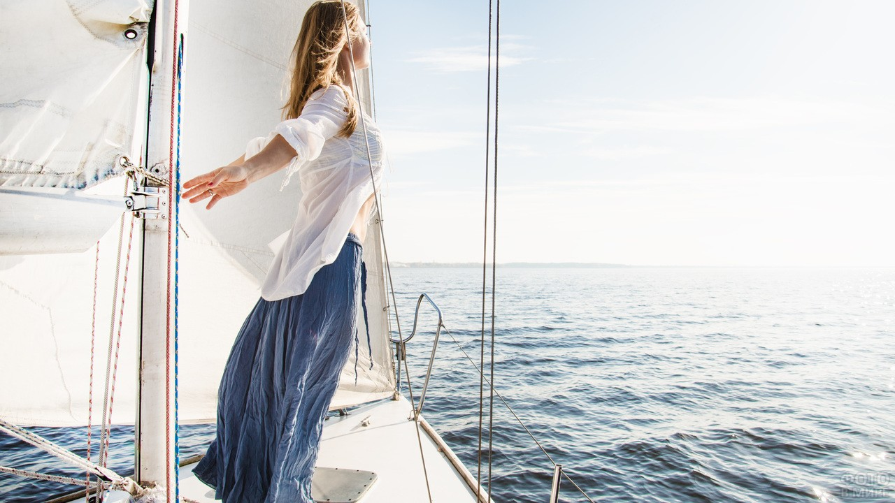 Девушка стоит на белой яхте