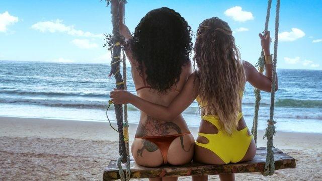 Две девушки в купальниках сидят на одной качели