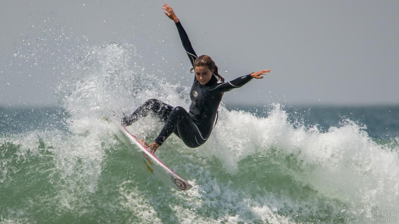Сёрфингистка в чёрном костюме на волне
