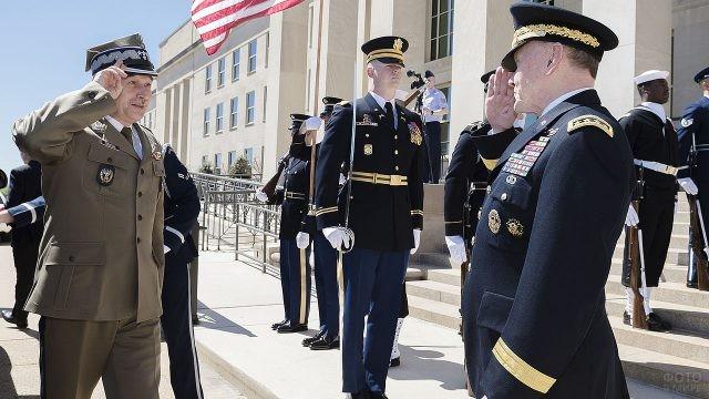 Военнослужащие отдают честь друг другу у здания Пентагона