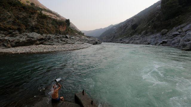 Мужчина обливается водой из ведра у реки Ганг