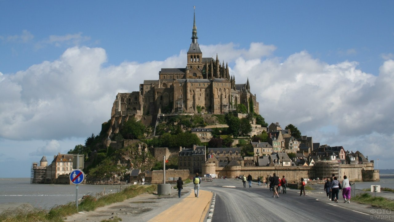 Туристы идут в крепость Мон-Сен-Мишель
