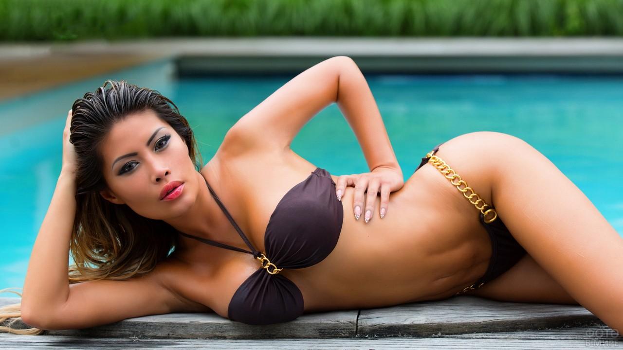 Азиатка в бикини на краю бассейна