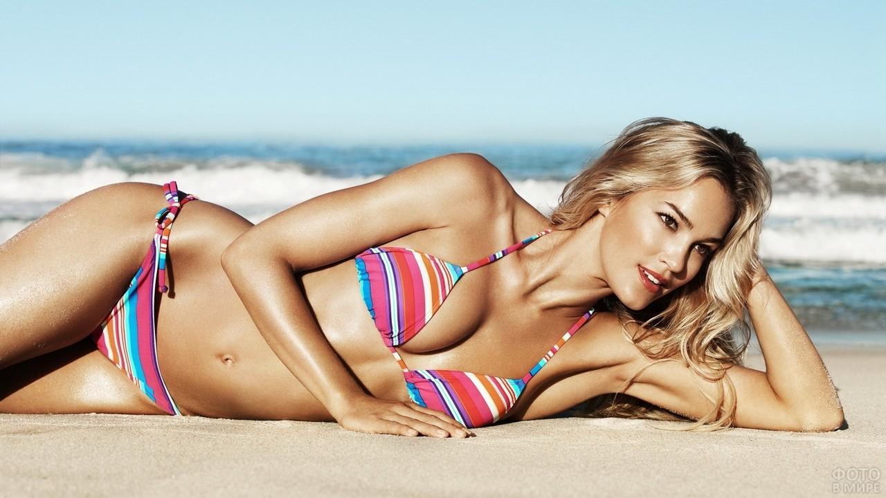 Блондинка лежит на песке