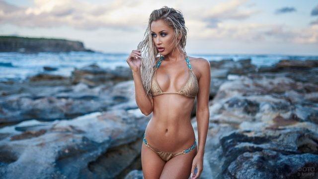 Блондинка с мокрыми волосами на камнях