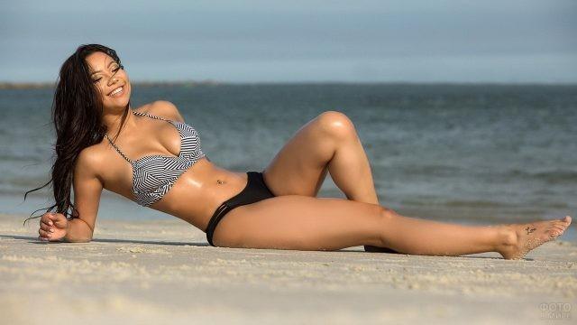 Брюнетка смеётся на пляже