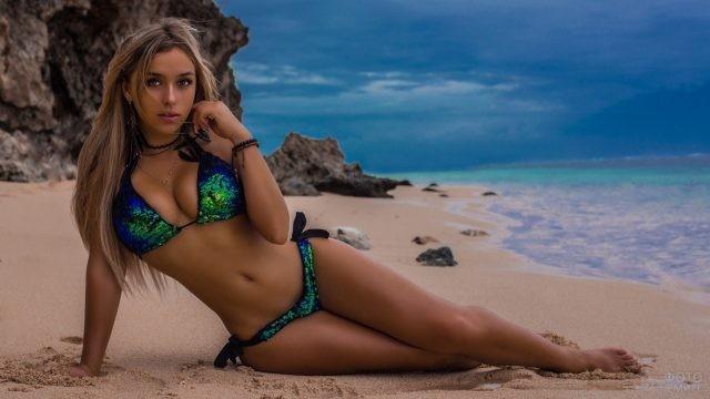 Девушка в блестящем купальнике у моря