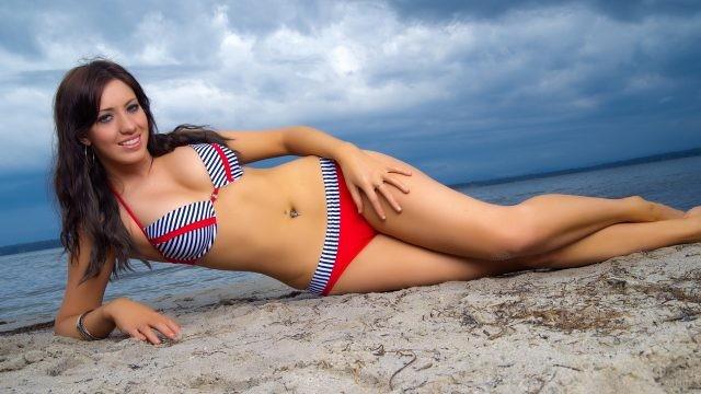 Улыбающаяся девушка лежит на песке