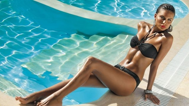Загорелая девушка возле бассейна