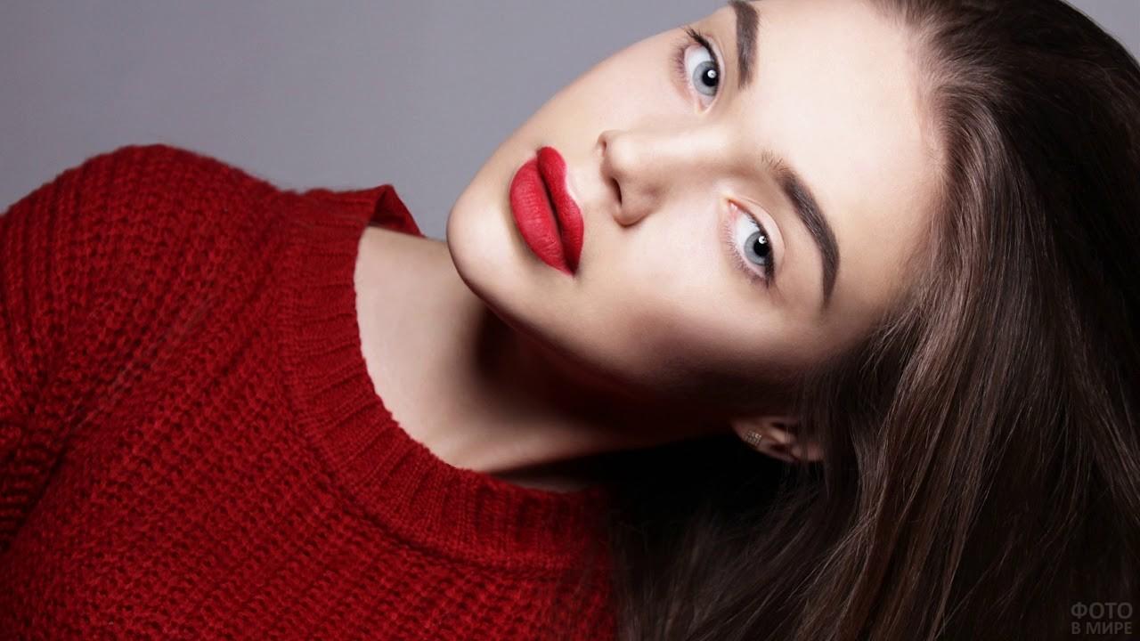 Длинноволосая девушка в красном свитере с алыми губами