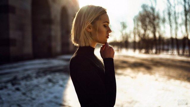 Блондинка касается рукой подбородка