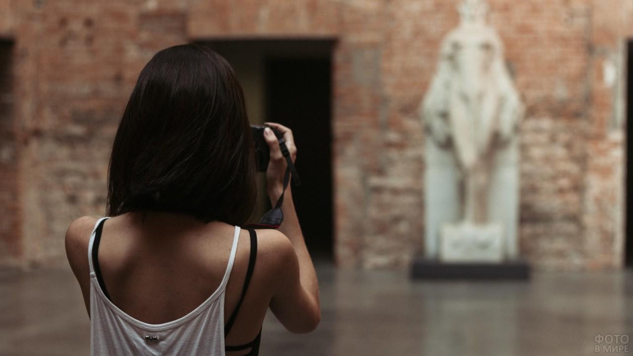Брюнетка фотографирует скульптуру