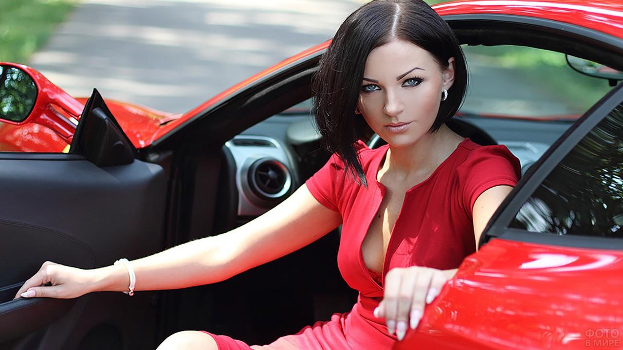 Брюнетка в красном платье сидит в автомобиле