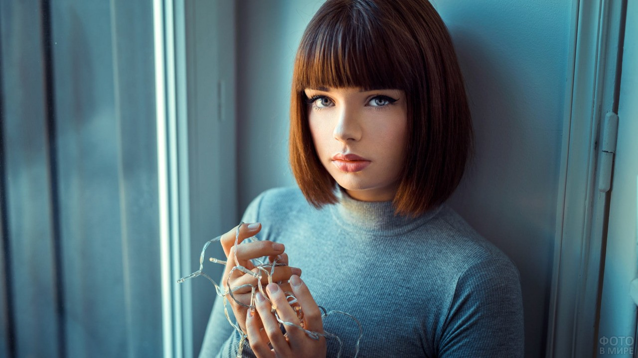 Девушка в водолазке с гирляндой в руках