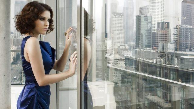 Кудрявая девушка в синем платье у окна