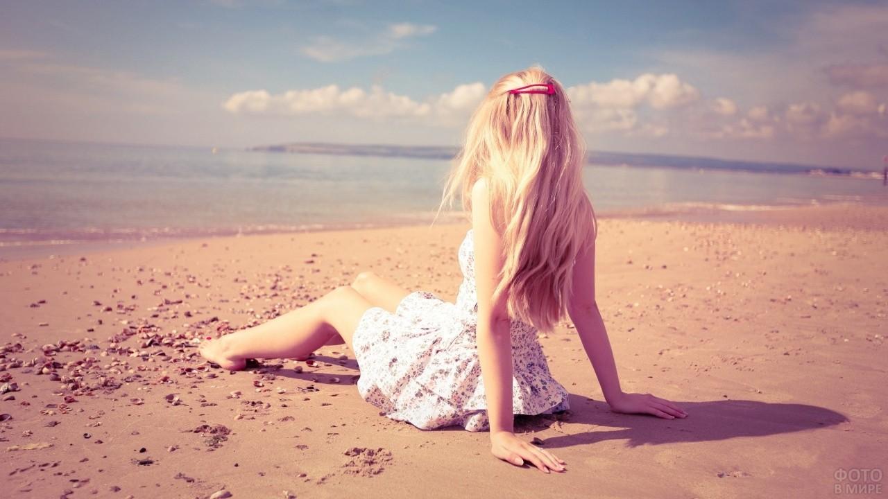 Блондинка с красной заколкой сидит на песке
