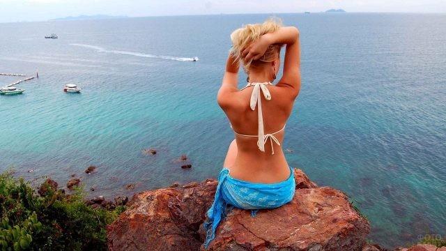 Блондинка с утёса смотрит на море