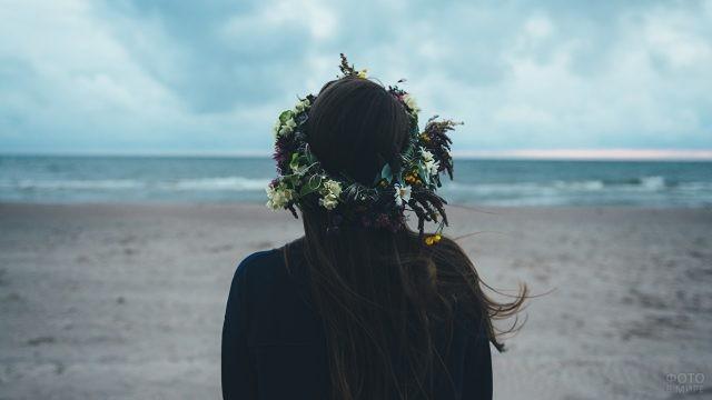 Брюнетка в венке смотрит на море
