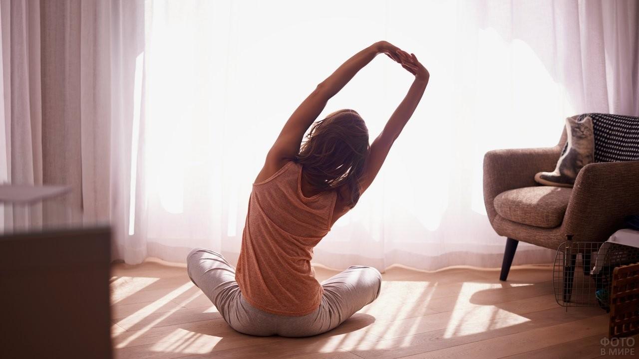 Девушка делает утреннюю гимнастику на полу