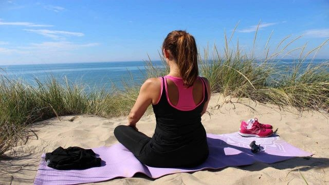 Девушка медитирует на диком пляже