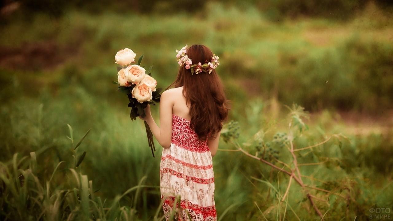 Девушка с цветами в руках и венком на голове