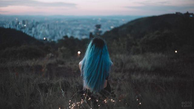 Девушка с синими волосами сидит на лугу