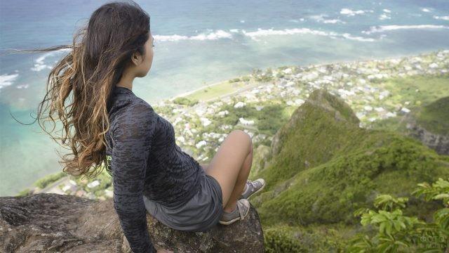 Девушка сидит на самом краю обрыва