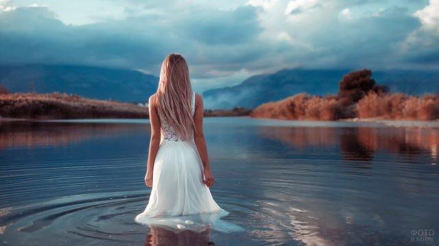 Девушка в белом платье зашла в воду