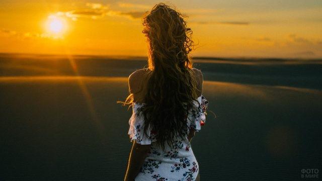 Девушка в цветастом платье смотрит на закат