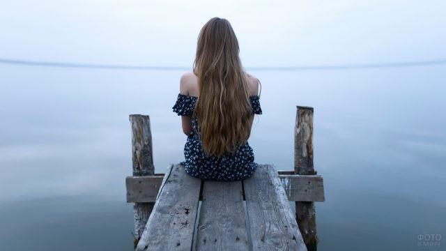 Одинокая девушка сидит у воды на мостике